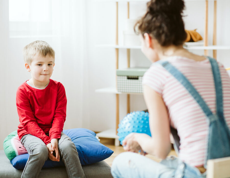 Young psychotherapist playing with little autistic boy during session